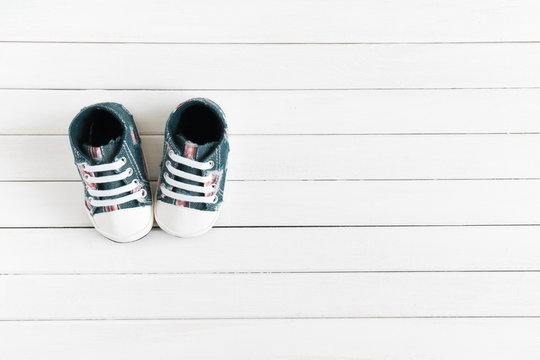 Baby sport shoes on wooden background, on a white board. Flat lay, top view, copy space