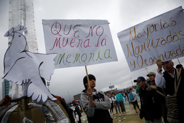 """A man carries a banner that reads """"Do not let memory die"""" while opposition supporters gather to take part in a rally on the day of the swearing-in of Colombia's new President Ivan Duque in Bogota"""