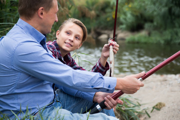 Portrait of smiling father with son having fish
