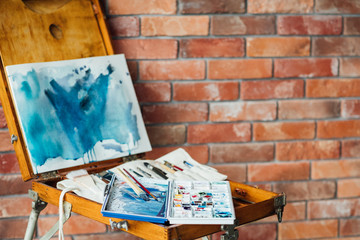 artist creative workspace. watercolor inks drawing instruments and tools on the easel. abstract blue picture.