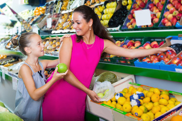 Cheerful female with daughter buying fresh apples