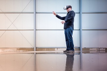 Construction worker standing at indoor construction site wearing vr eyeglasses or goggles, bright environment with space for your copytext or imagery projection