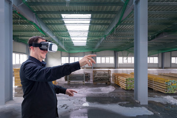 Construction worker at indoor construction site wearing vr eyeglasses or goggles and gesturing