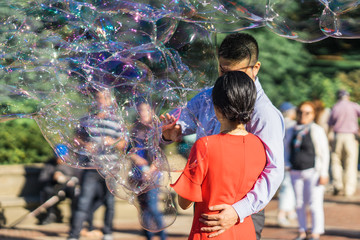 Couple playing with giant rainbow soap bubbles floating in the summer air during a beautiful sunny day. Fun entertaining game for kids and adults.
