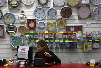 A vendor stands in front of products imported from China at a store in Rio de Janeiro
