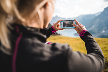 Adventurous Hiker Girl in the Austrian Alps capturing a beautiful landscape with her smartphone