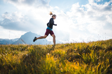 Sportive girl running on a trail through a beutiful Mountain Meadow in the Austrian Alps