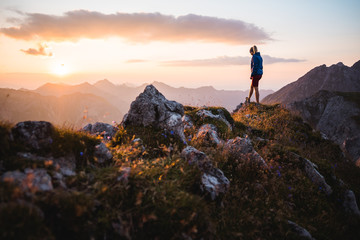 Hiker girl enjoying a sunset on top of a peak Wall mural