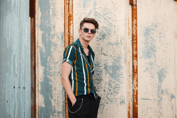 Young handsome guy with fashionable sunglasses in a stylish beach green shirt near the metal wall