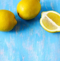 Fresh lemons on blue wooden background