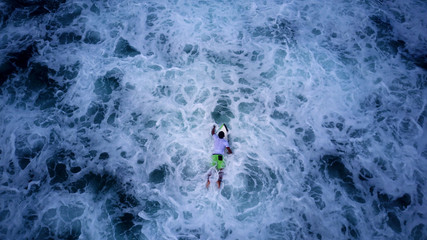 AERIAL SHOT: Surfer paddling on a white board, waiting for a big wave to ride