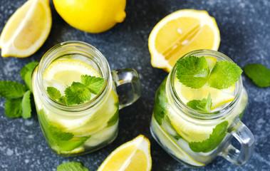 Mason jar glass of lemonade with mint on blue stone background