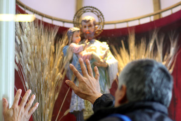 Argentine Catholics touch the glass in front of a statue of San Cayetano, the patron saint of labour and bread, during his feast day at San Cayetano church in Buenos Aires