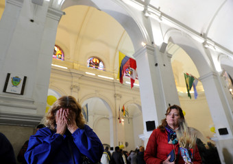 A woman reacts as she attends celebrations of San Cayetano, the patron saint of labour and bread, at San Cayetano church in Buenos Aires