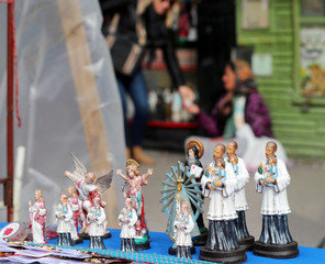 Figurines of San Cayetano, the patron saint of labor and bread, are displayed for sale as a woman begs for money during the saint's feast day at San Cayetano church in Buenos Aires