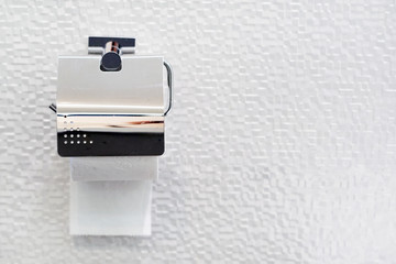 A white roll of soft toilet paper neatly hanging on a modern chrome holder on a light bathroom wall. copy space