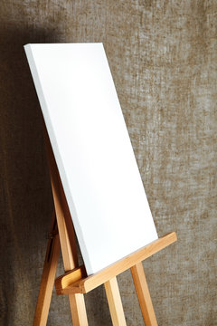 pure white synthetic canvas stretched on a wooden stretcher standing on a wooden easel for artists. On sackcloth fabric texture background. Art, creativity, hobby, job and creative occupation concept