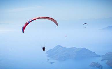 Foto op Canvas Luchtsport Parachute skydiver flying in clouds at top of mountains