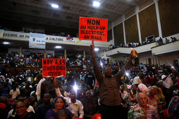 Opposition supporters hold up placards during protest against what they say were vote count irregularities in Bamako