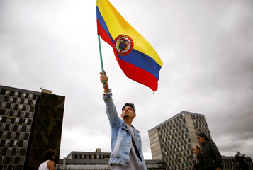 An opposition supporter waves a national flag as the swear-in ceremony of Colombia's new President Ivan Duque takes place, in Bogota