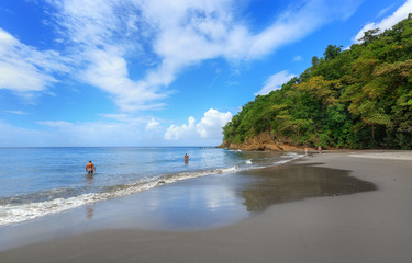 Black Sand beach in Martinique, Caribbean. Anse Couleuvre, Le Precheur Region, near Motagne Pelee. People in water looking to turtles.