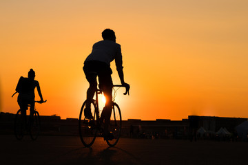 man and woman riding bicycle with sunset sky background
