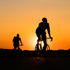 silhouette of couple riding  bicycle with sunset sky background