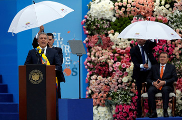 Colombia's new President Ivan Duque (L) addresses the audience during his swearing-in ceremony at  Bolivar Square in Bogota