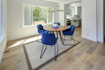Modern dining room with wood table and blue chairs.