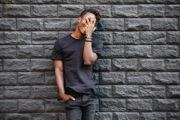 African american man in black t-shirt laughing against brick wall, palm on face