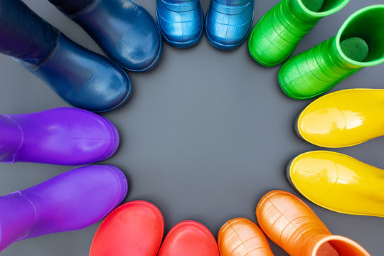 Colorful rubber boots of all colors of the rainbow-red, orange, yellow, green, blue, cyan and purple stand on the gray surface in a circle. Top view, space for text.