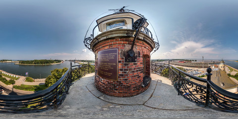 panorama 360 degrees angle view from above of the sea lighthouse at the port and sea warehouses in equirectangular projection, skybox VR AR content
