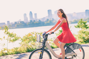 City bike young woman biking riding bicycle in street summer outdoor with Montreal skyline. Happy multiracial Asian girl active living a healthy lifestyle. Urban commute going to work.