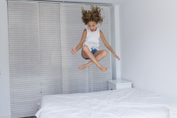 beautiful kid girl playing and jumping on bed. Fun indoors. Family love and lifestyle