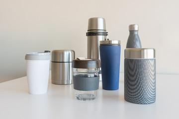 Collection of reusable food and drink containers on white table - sustainability concept (selective focus)