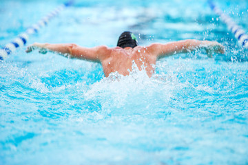 Man swimming butterfly stroke in a race, focus on waves, swimmer is out of focus