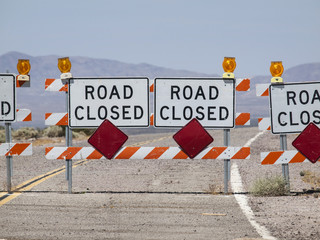 Highway road closure signs and barricades near Route 66 in the California Mojave Desert.