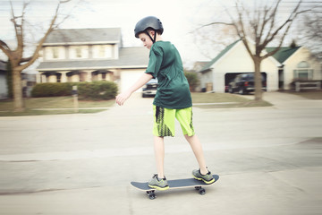 Boy wearing a helmet riding a skateboard, motion blurred image