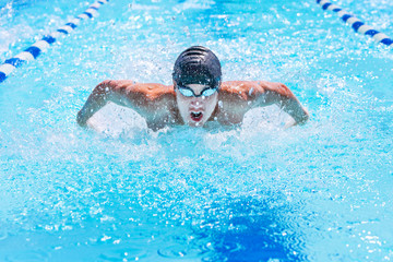 Teenage swimmer swimming butterfly stroke in a race