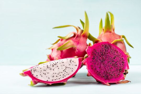 Half and slice dragon fruit on color background, tropical fruit