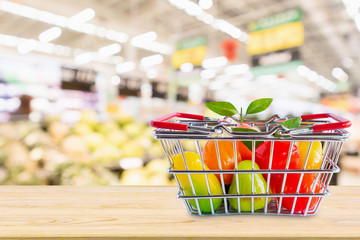Shopping basket with fruits on wood table over grocery store supermarket blur background