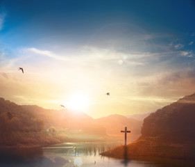 Christ Jesus birth and resurrection concept :Silhouette cross on Calvary mountain sunset background