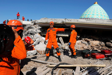 Rescue team members prepare to find people trapped inside a mosque after an earthquake hit on Sunday in Pemenang
