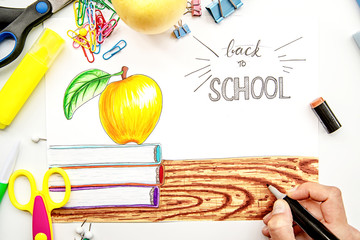 female hand drawing an illustration with markers white background with books, apple and lettering back to school