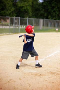 Young Boy Swinging Baseball Bat at Ball in Youth Ragball Game