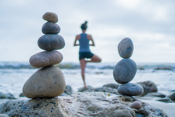 Printed roller blinds Stones in Sand Beautiful girl tree pose yoga by the ocean with stacking rocks