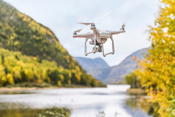 Drone flying in beautiful fall nature landscape background. Technology toy device.