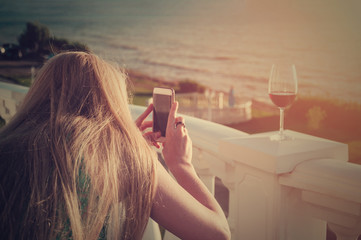 Blonde young woman with long natural hair standing on balcony near the sea and using mobile phone to take photo