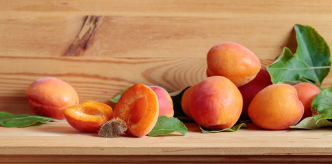 Apricots with leaves on a wooden table.