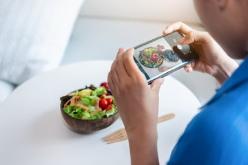 A woman is using smartphones to take photos to post a salad she made in her social.